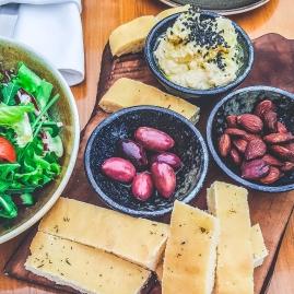 Hummus, oliwki, prażone migdały i chlebek kukurydziany